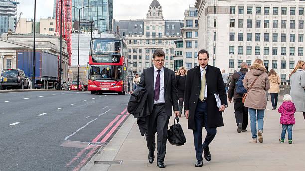 Two Businessmen Walking Across London Bridge stock photo