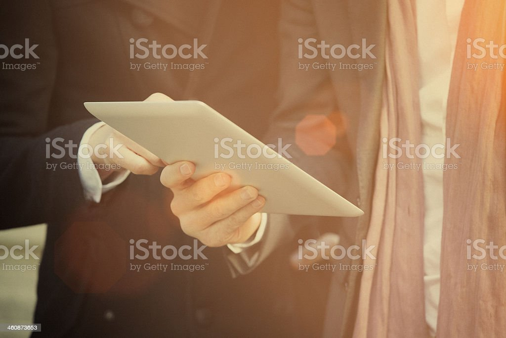 Two businessmen watching on a digital tablet stock photo