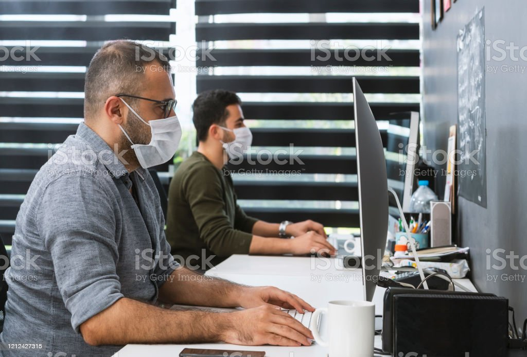 Two businessmen with protective face masks are working in the office Two businessmen with protective face masks are working in the office 25-29 Years Stock Photo