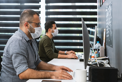 Two Businessmen With Protective Face Masks Are Working In The Office Stock Photo - Download Image Now