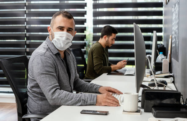 Two businessmen with protective face masks are working in the office stock photo