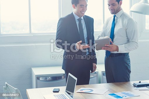 496441730 istock photo Two businessmen working on a digital tablet. 664458922