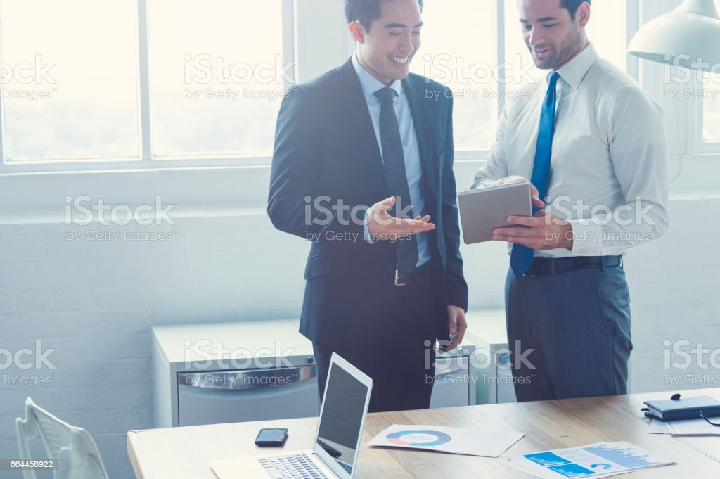 Two businessmen working on a digital tablet. stock photo