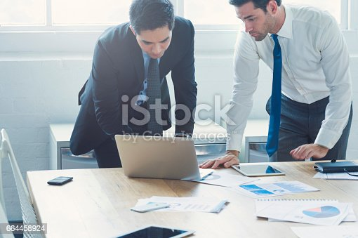 496441730 istock photo Two businessmen working on laptop computer. 664458924