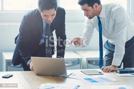496441730 istock photo Two businessmen working on laptop computer. 664458946