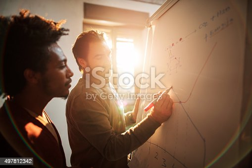 497812268 istock photo Two businessmen working together on a business graph at office. 497812342