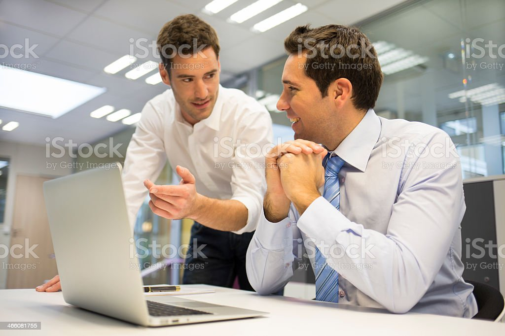 Two businessmen working with using one PC at office royalty-free stock photo