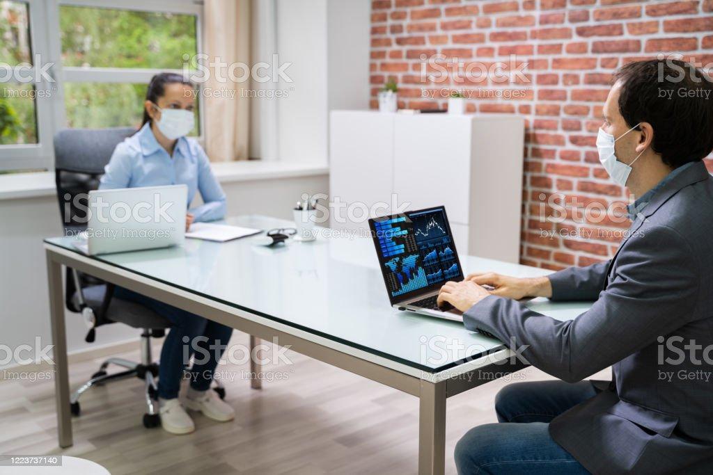 Zwei Geschäftsleute analysieren Finanzdiagramm auf Laptop - Lizenzfrei Abstand halten - Infektionsvermeidung Stock-Foto
