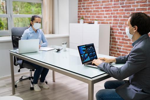 Zwei Geschäftsleute Analysieren Finanzdiagramm Auf Laptop Stockfoto und mehr Bilder von Abstand halten - Infektionsvermeidung