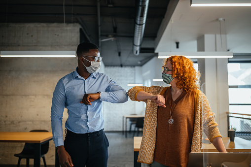 Two businesspeople elbow bumping while greeting each other in the office during COVID-19 epidemic.