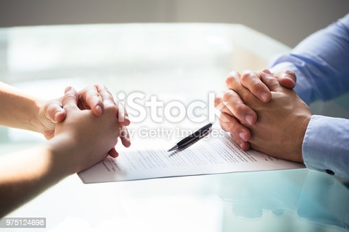 Close-up Of Two Businesspeople Hand With Document On Desk