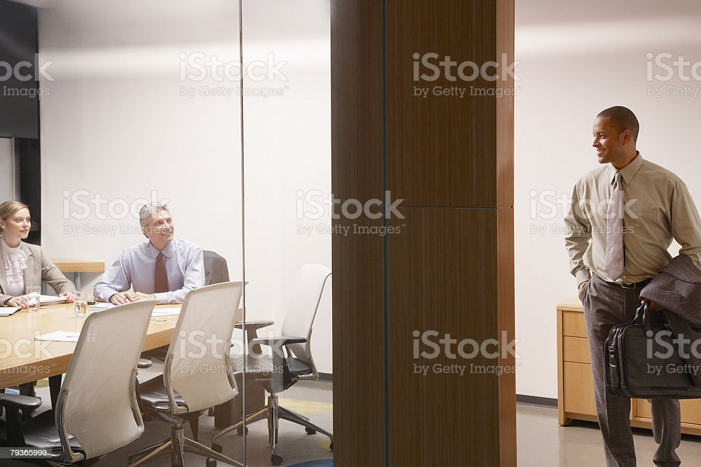 Two businesspeople in boardroom watching businessman leave royalty-free stock photo