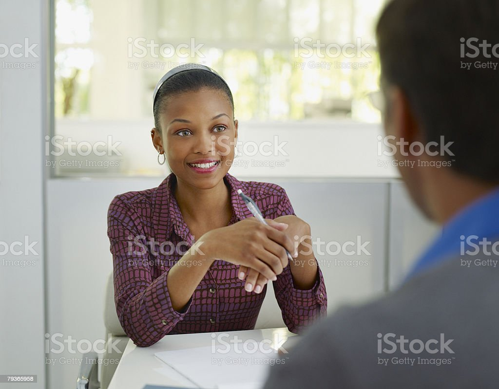 Two businesspeople in office with notepad stock photo