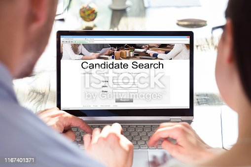 Two Businesspeople Looking At House On Laptop Screen