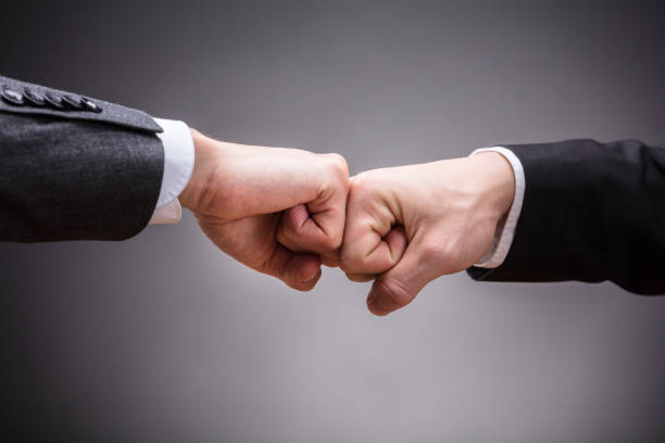 two businesspeople making fist bump - knuckle stock photos and pictures