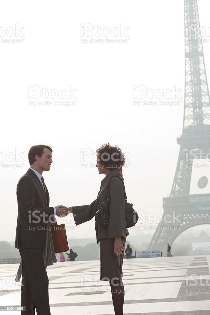 Two businesspeople outdoor shaking hands by Eiffel Tower stock photo