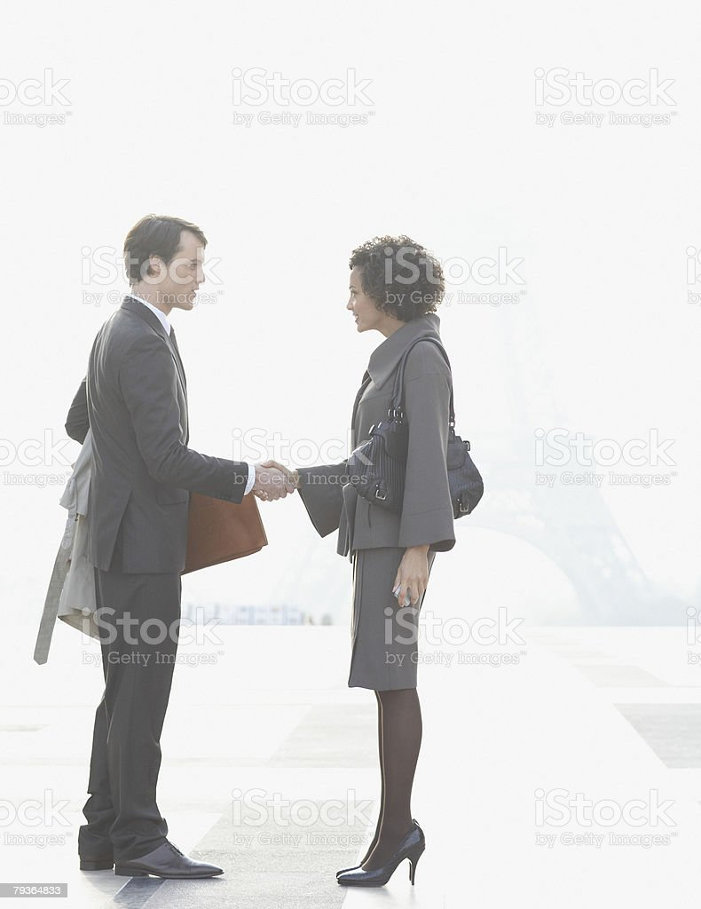 Two businesspeople outdoor shaking hands by Eiffel Tower royalty-free stock photo