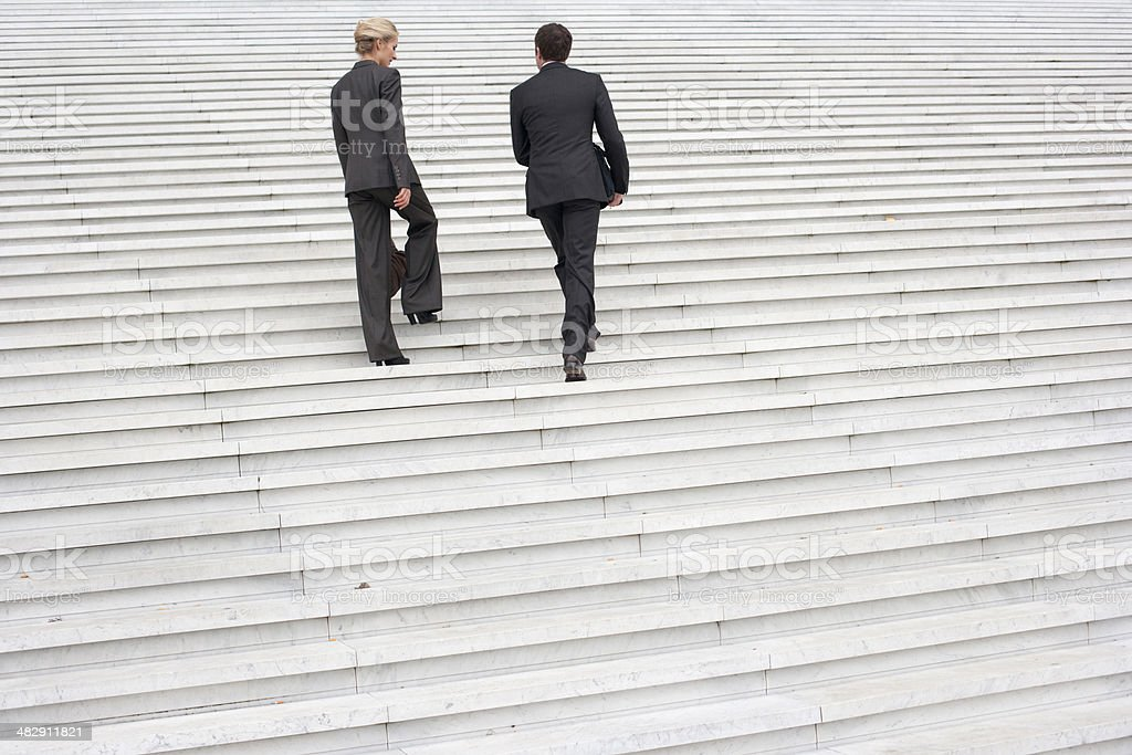 Two businesspeople outdoors going up staircase stock photo