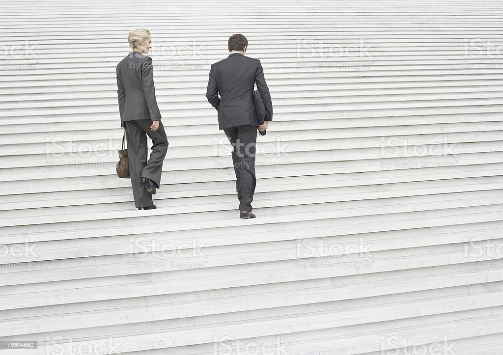 Two businesspeople outdoors going up staircase royalty-free stock photo