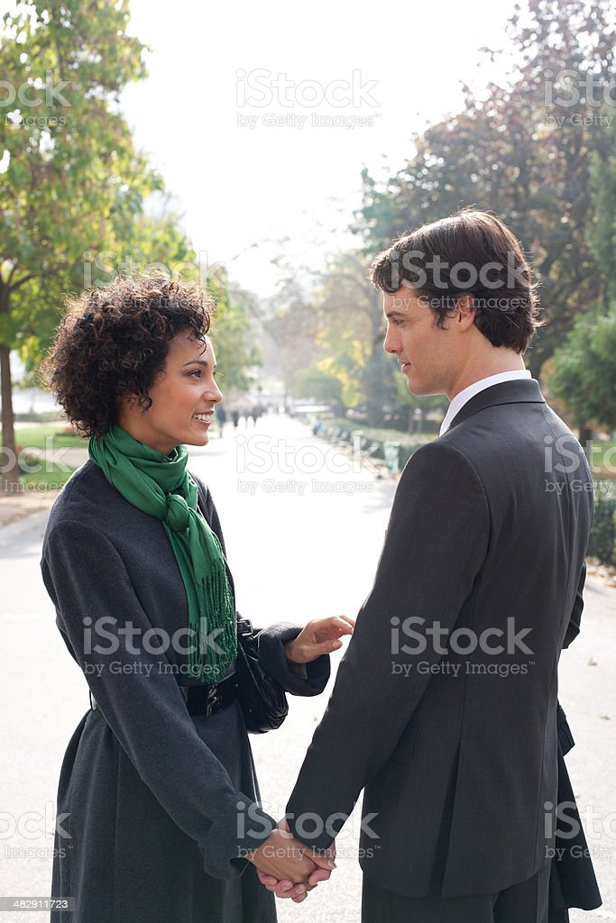 Two businesspeople outdoors holding hands looking each other stock photo