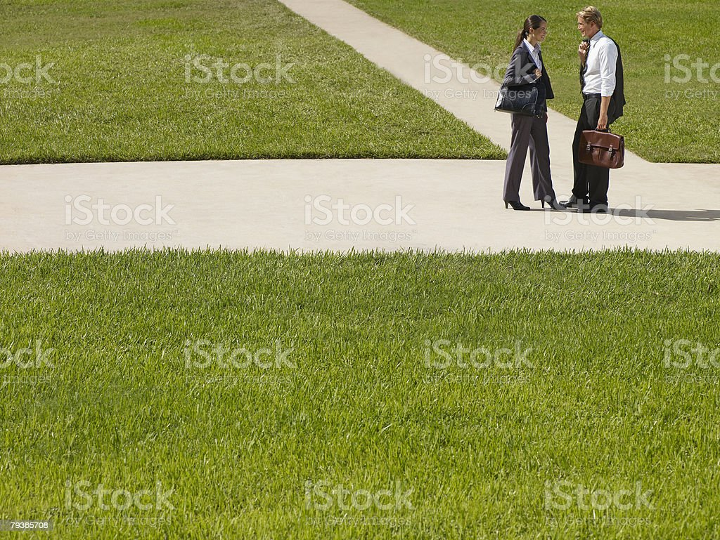 Two businesspeople outdoors on sidewalk talking royalty-free stock photo