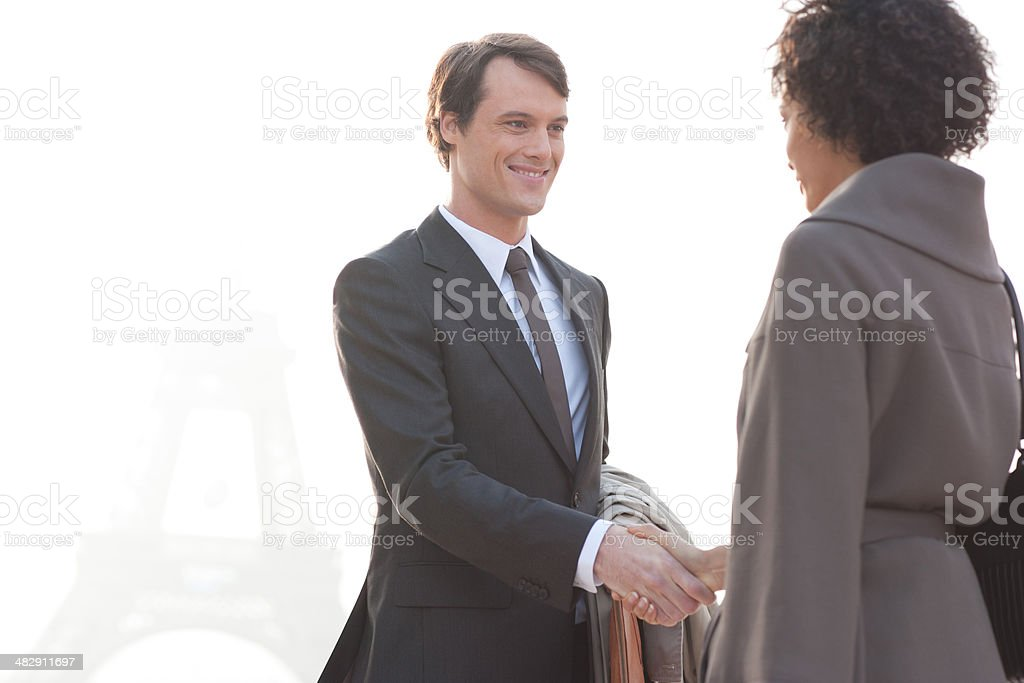 Two businesspeople outdoors shaking hands by Eiffel Tower stock photo