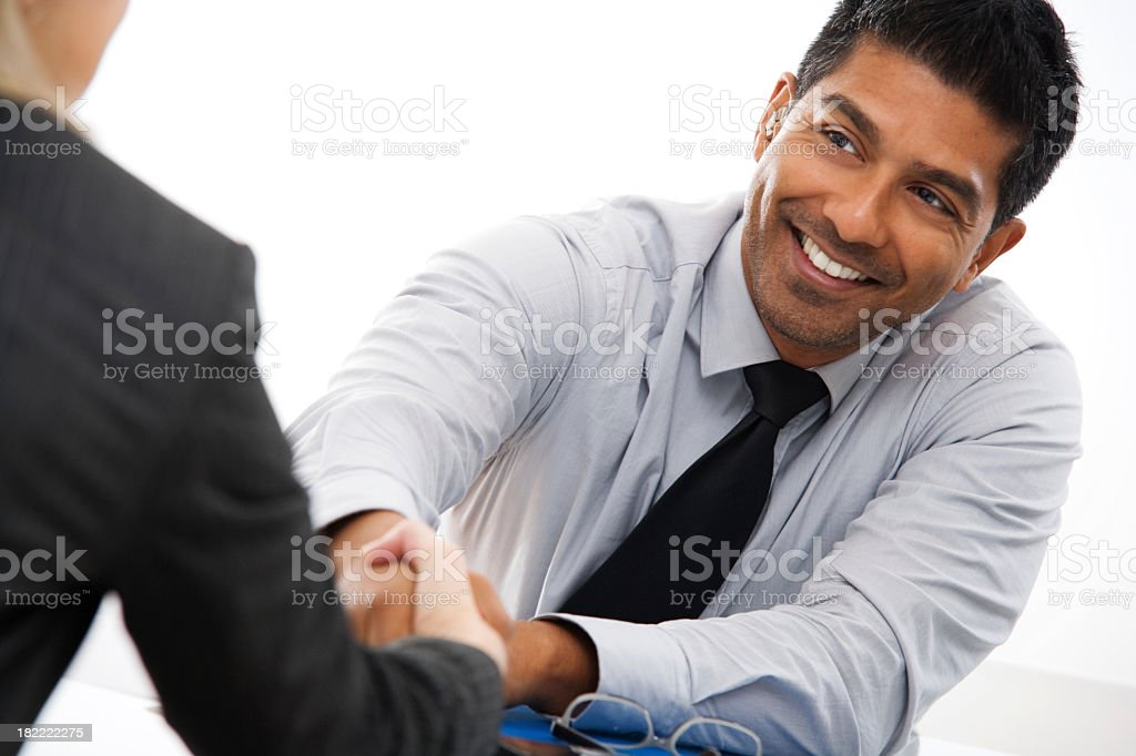 Two businesspeople shaking hands across a desk stock photo