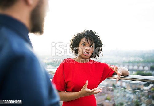 istock Two businesspeople standing against London view panorama. 1059594956