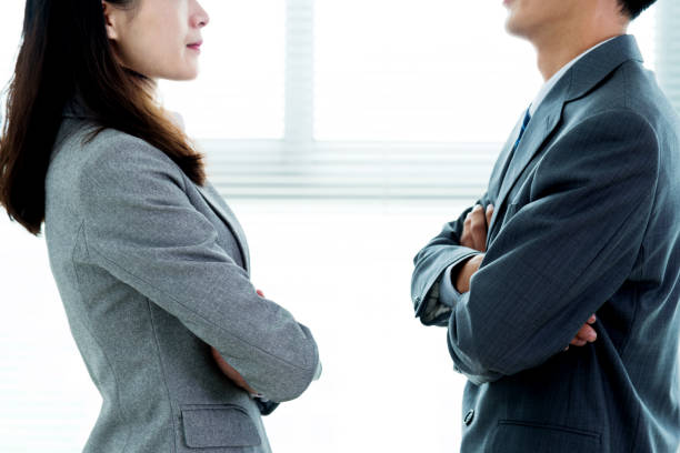 two businesspeople standing face to face - battle of the sexes concept stock pictures, royalty-free photos & images
