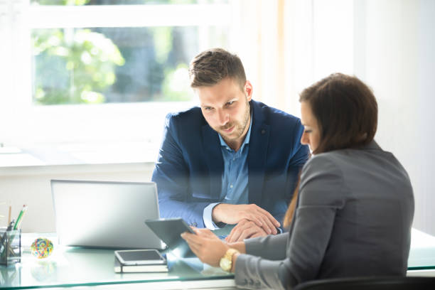 two businesspeople using digital tablet - bankers stock photos and pictures