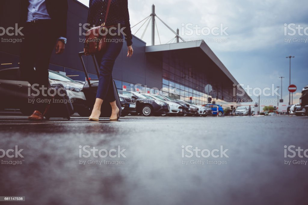 Two businesspeople walking in airport parking lot stock photo