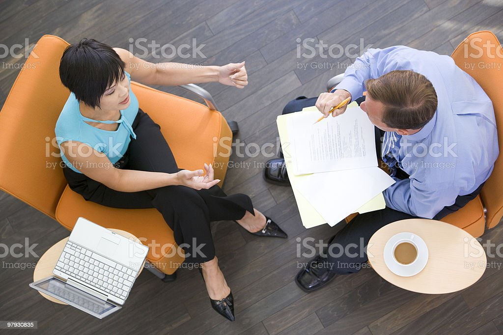 Two businesspeople with coffee laptop and folder stock photo