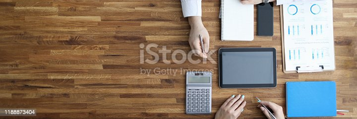 Two businesspeople work in ofiice on wooden table top view background. Business seminar education concept.