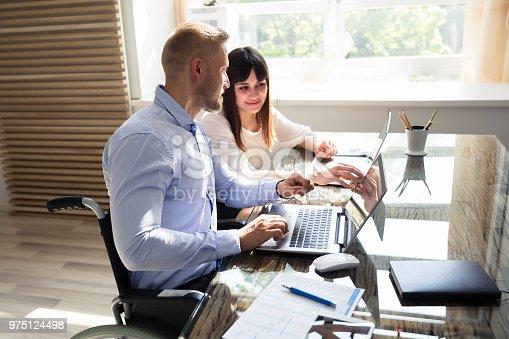 1144373653 istock photo Two Businesspeople Working On Laptop 975124498
