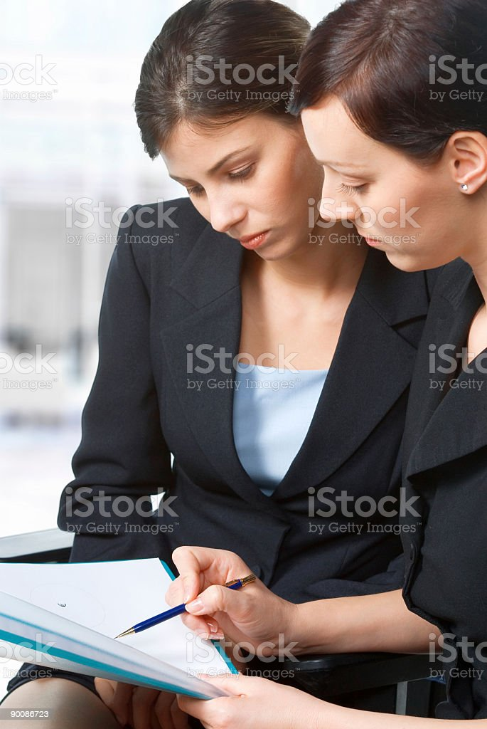 Two businesswoman in a meeting reviewing documents royalty-free stock photo