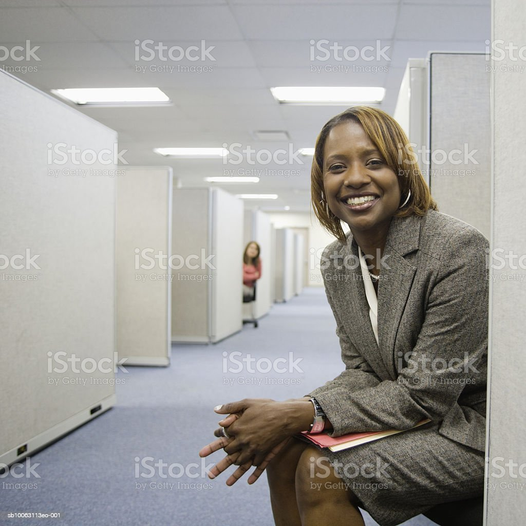 Two businesswoman in cubicle, smiling (focus on foreground) Lizenzfreies stock-foto