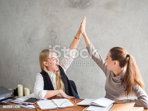 1031394114 istock photo Two businesswoman smile and raise hands up, feeling happy on Friday, complete finish job, successful/achievement working in office concept 869981406