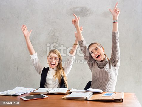 1031394114 istock photo Two businesswoman smile and raise hands up, feeling happy on Friday, complete finish job, successful/achievement working in office concept 869981468