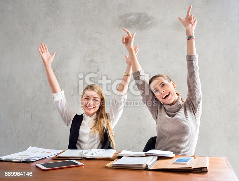 1031394114 istock photo Two businesswoman smile and raise hands up, feeling happy on Friday, complete finish job, successful/achievement working in office concept 869984146