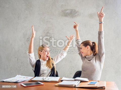 1031394114istockphoto Two businesswoman smile and raise hands up, feeling happy on Friday, complete finish job, successful/achievement working in office concept 869984198