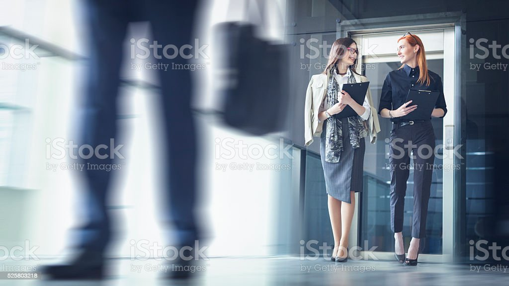 Two businesswoman walking and talking stock photo