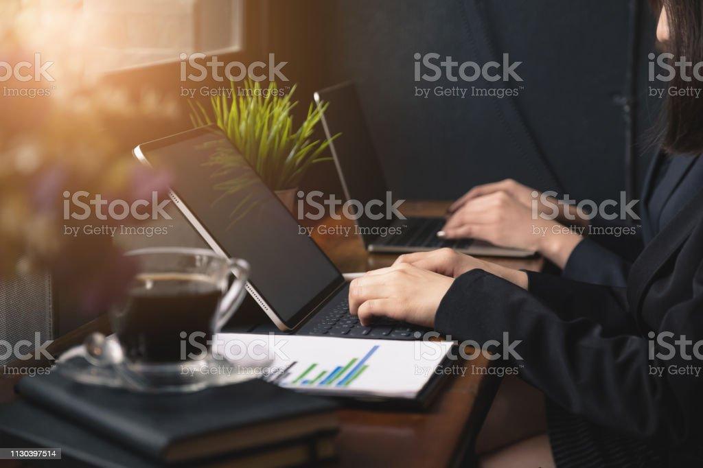 Zwei Geschäftsfrau arbeiten und kommunizieren, während sie gemeinsam am Schreibtisch sitzen. – Foto