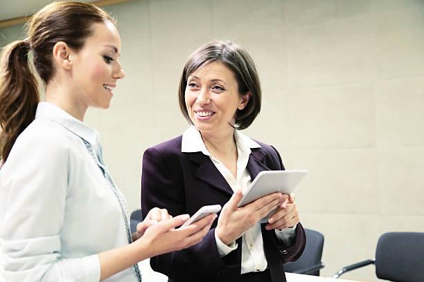 Dos empresaria trabajando con dispositivos móviles - foto de stock