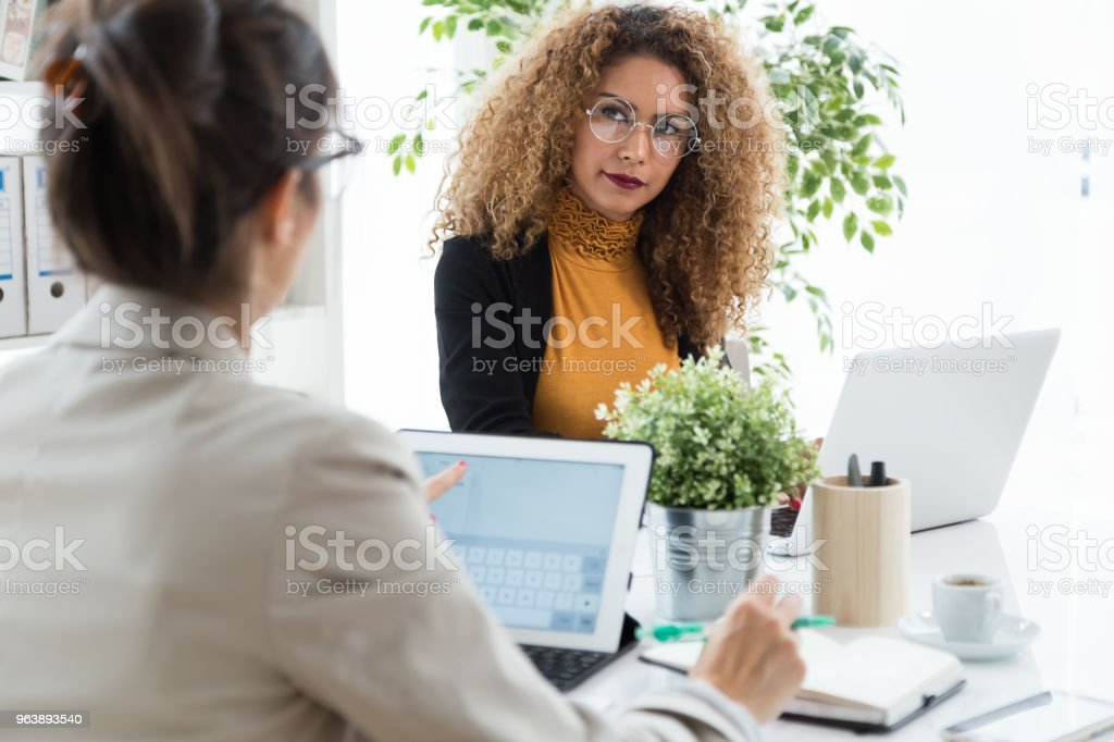 Two businesswoman working with laptop in her office. - Royalty-free Achievement Stock Photo