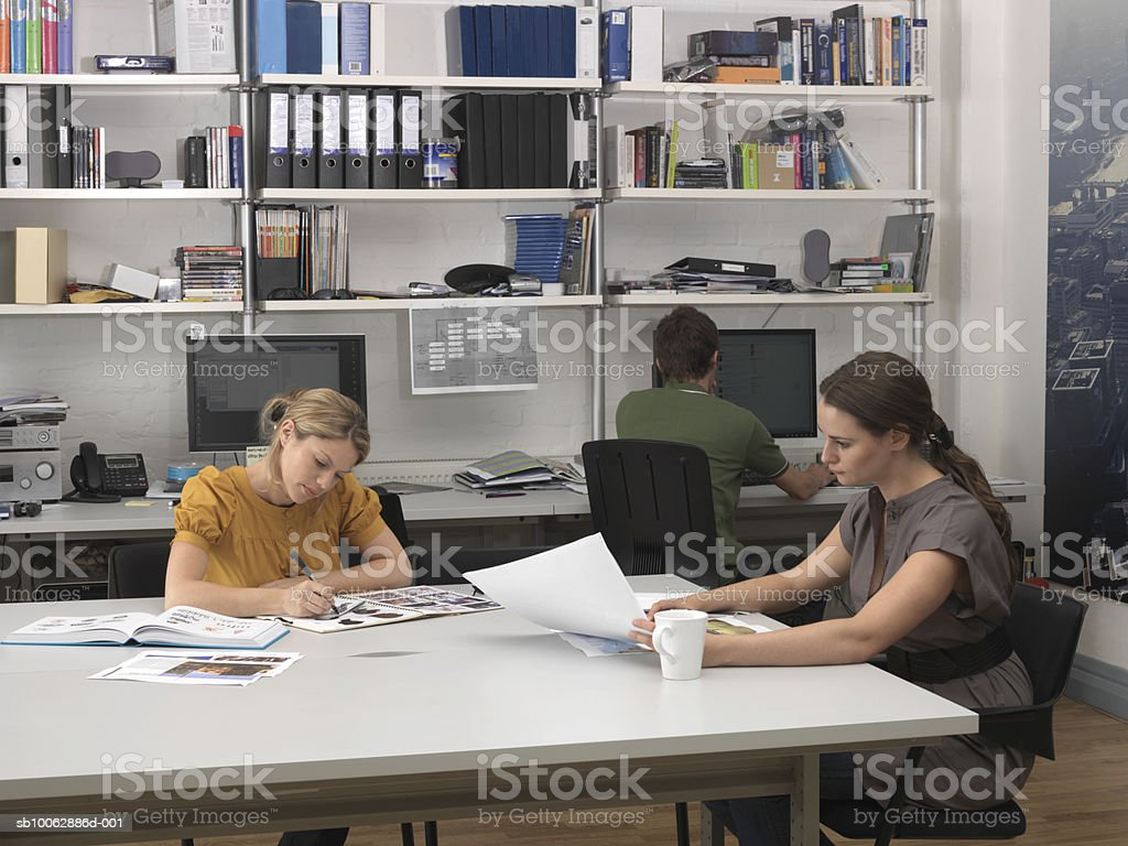 Two businesswomen and man working in open plan office Lizenzfreies stock-foto