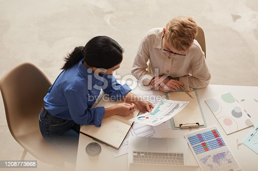 High angle view at two modern businesswomen discussing data charts while sitting at table, copy space