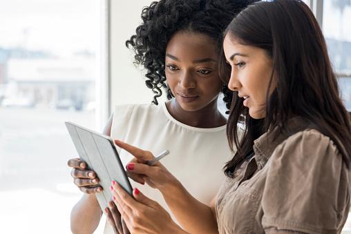 istock Two businesswomen holding digital tablet, Hispanic woman pointing 626468810