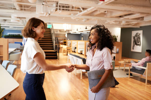Two Businesswomen Meeting And Shaking Hands In Modern Open Plan Office stock photo