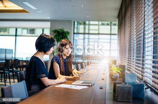 istock Two businesswomen on meeting using online data 604353232