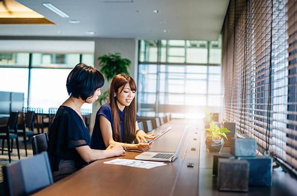 Two businesswomen on meeting using online data stock photo